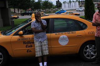 Image of Taxi driver leaning on his yellow cab