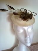 Mini sombrerito en beige con plumitas de faisan.