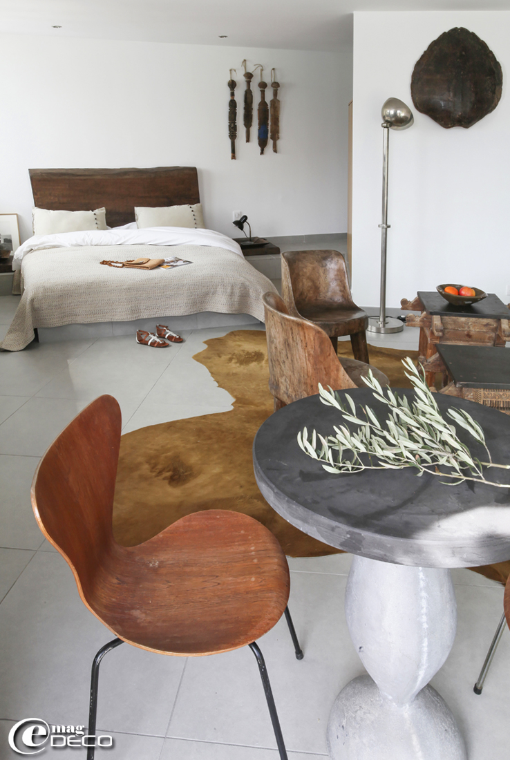 Une chambre de la maison d'hôtes 'La Suite Cassis' décorée dans un esprit ethnique, table ronde en béton moulé 'DMI' entourée de chaises '3107' dessinées par Arne Jacobsen