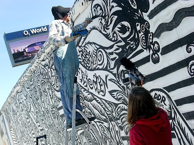 Maler saniert Mauersegment, Frau filmt