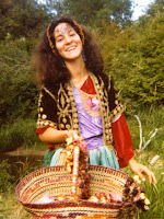 Hippie woman holding a basket and dressed in dirndl outfit 