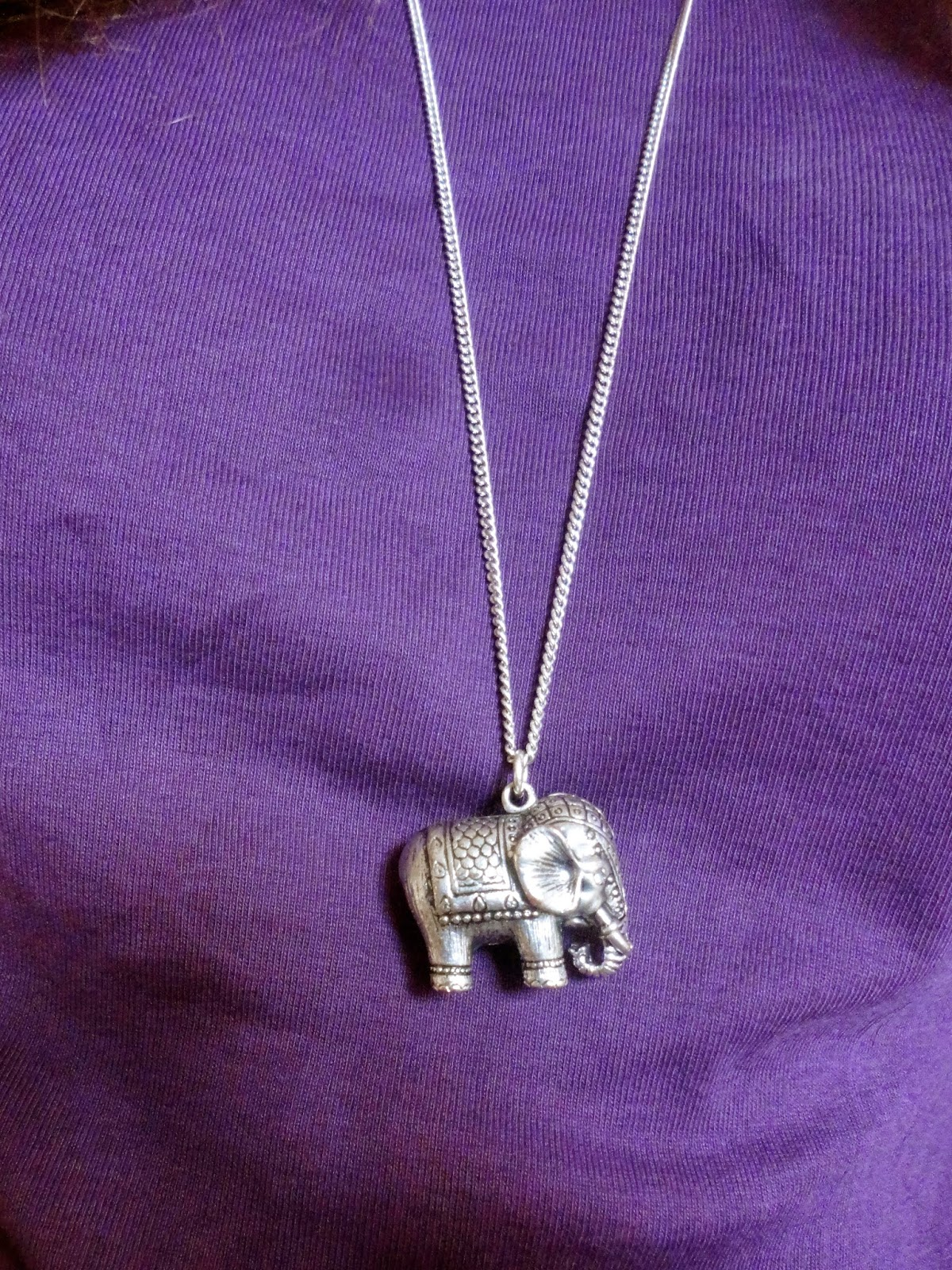 silver elephant pendant necklace on purple top