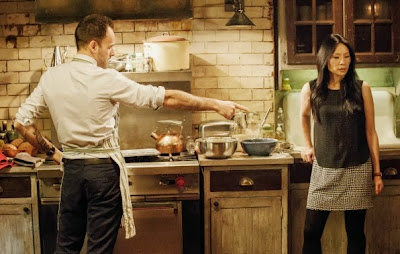 Jonny Lee Miller as Sherlock Holmes wearing apron and making a Yorkshire pudding with Lucy Liu as Joan Watson in the kitchen in brownstone in CBS Elementary Season 2 Episode 10 Tremors
