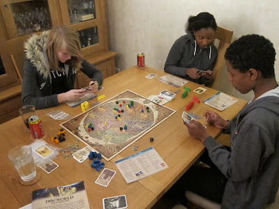 Discworld: Ankh-Morpork - The players consider what cards they wish to play next