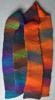 Two slip stitch scarves lying side-by-side; made from colour-changing yarn; left: blues, greens & dark greys; right: fiery oranges, reds and charcoal.