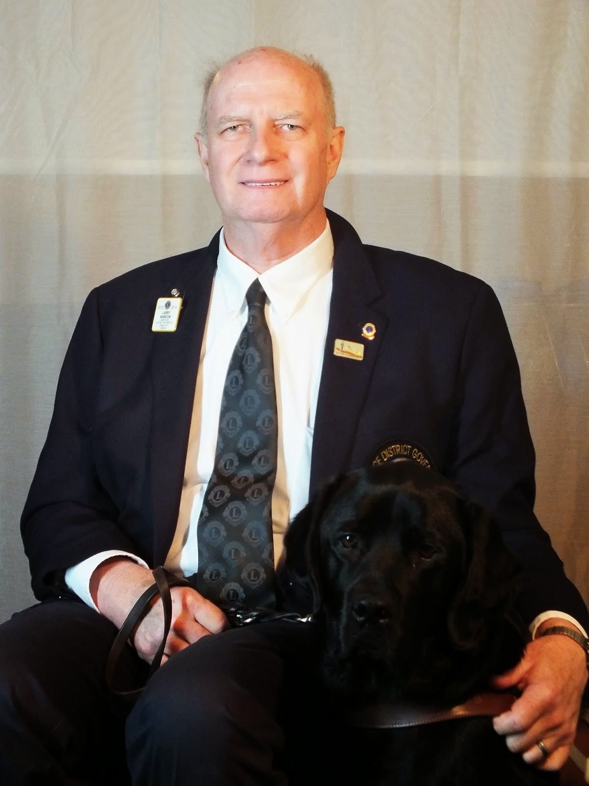 Portrait of Larry (wearing a dark suit and tie) sitting while proudly posing with his guide dog Brinkley (black Lab in harness).