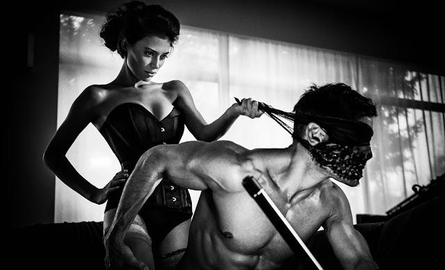 Imagen en blanco y negro de una sensual mujer dominando eróticamente a un hombre