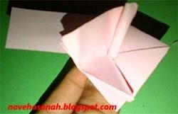 gulung ujung lipatan kertas dan selipkan pada lubang