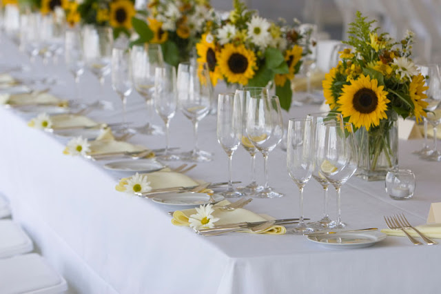 This just makes me happy. Sunflowers, glistening silver, white linens ...