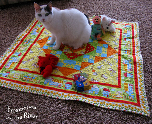 Bella playing on the Happy Town quilt