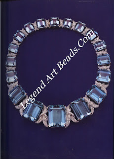 A necklace of graduated aquamarines, tooling 553 carats, connected with diamond ribbons.