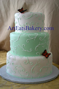 Three tier mint green and white custom unique wedding cake design with curlicues and edible butterf