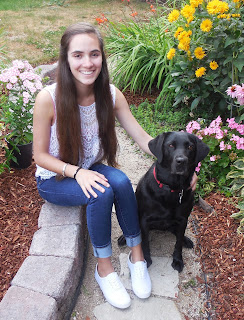 Mikaela smiles sitting next to a black Lab.