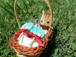 Boucles d'oreille en forme de sucettes bleu-vertes en pâte Fimo, ornées d'un ruban rouge et d'une petite tranche de pomme, placées dans un panier devant un petit écureuil