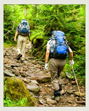 Two people hiking up a mountain with packs on their back