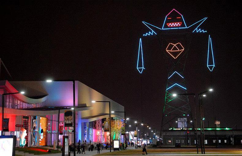 Este gigante torre de la línea eléctrica es un robot que puede expresar sus estados de ánimo con luces de neón
