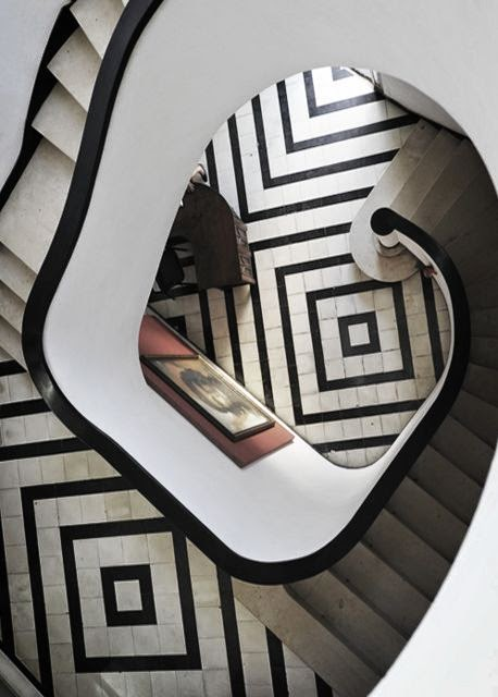 gorgeous circular stair case foyer with black and white tile geometric pattern