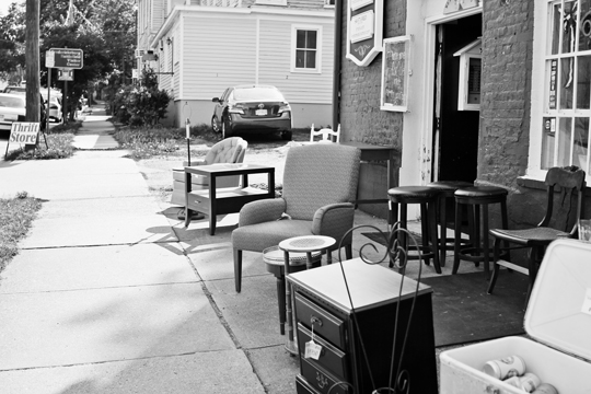 Black and white photo of a thrift store sidewalk sale in Fredericksburg, VA