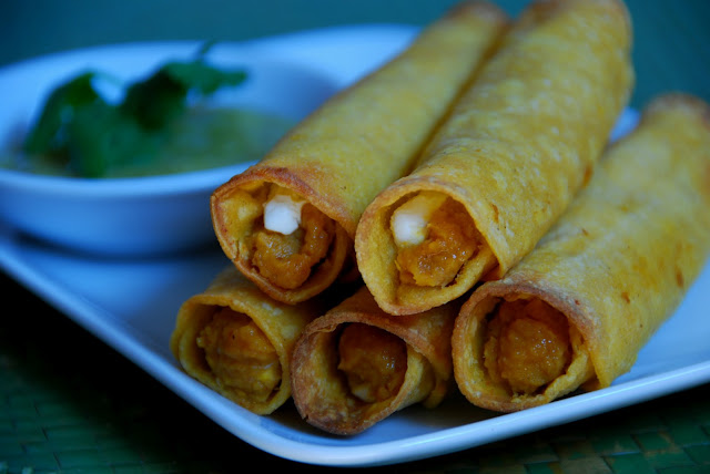 close up of 5 rolled taquitos on white plate with cup of salsa
