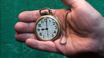 Man's hand holding a gold Hamilton trainman's pocketwatch