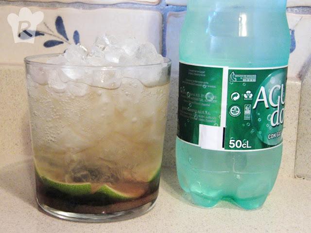 Añade ron, hielo picado y agua con gas