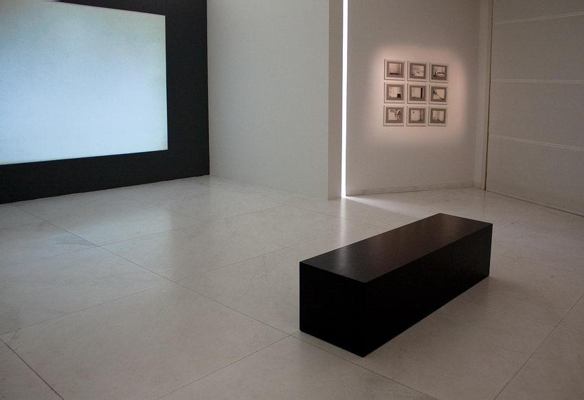 Sala com um écrã à esquerda, branco mas sem imagem. À direita um conjunto de quadros na parede e no meio da sala um paralelipípedo enorme