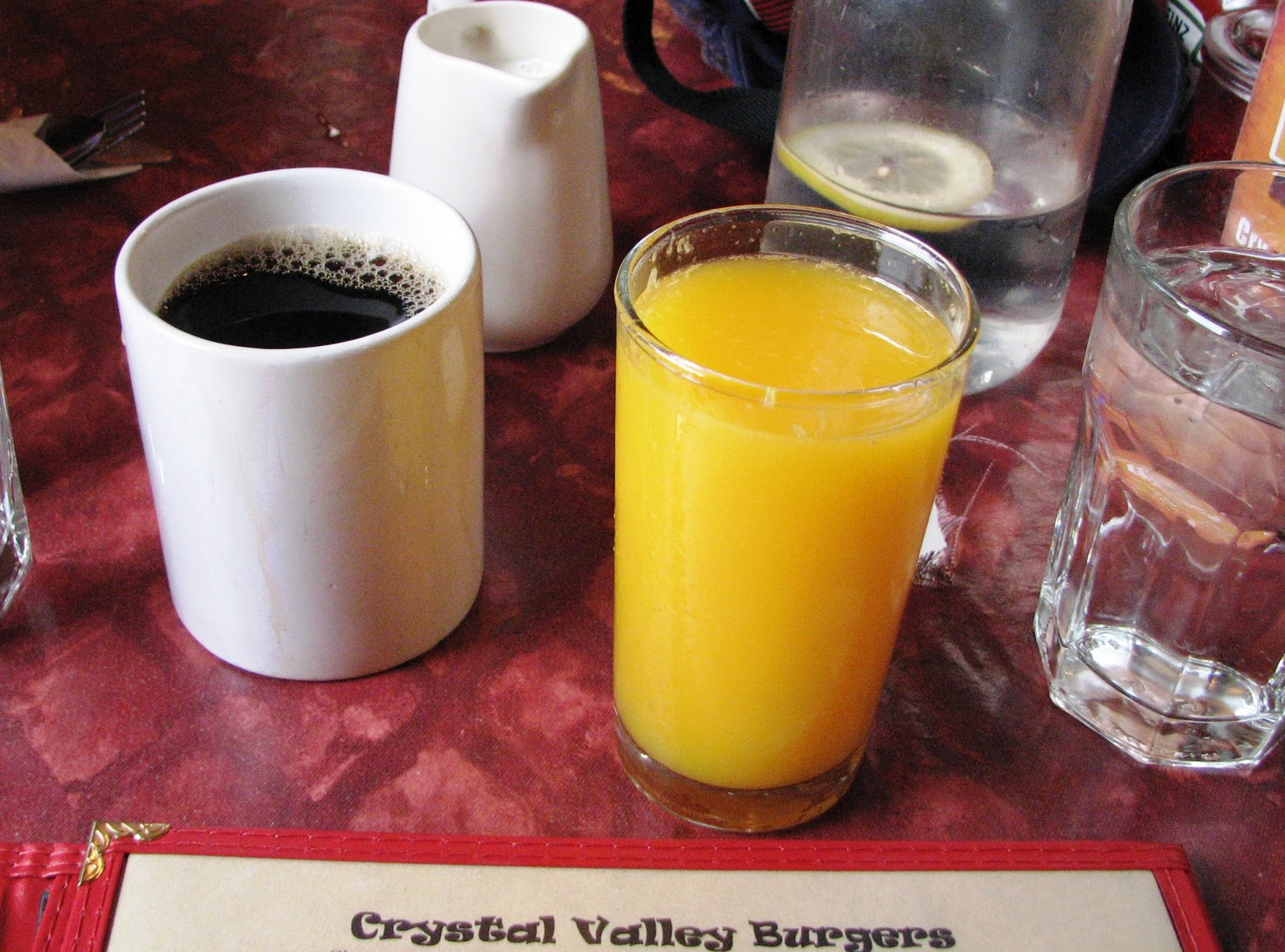 person drinks both coffee and orange juice for breakfast