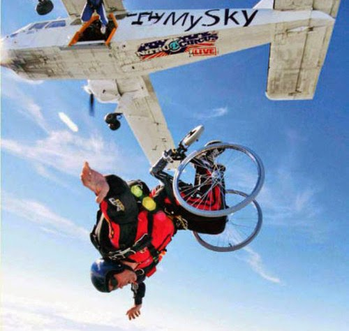 person in a wheelchair having just jumped out of an airborne airplane