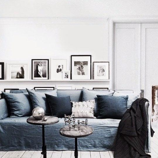 Sofa w salonie i białe pulki na książki