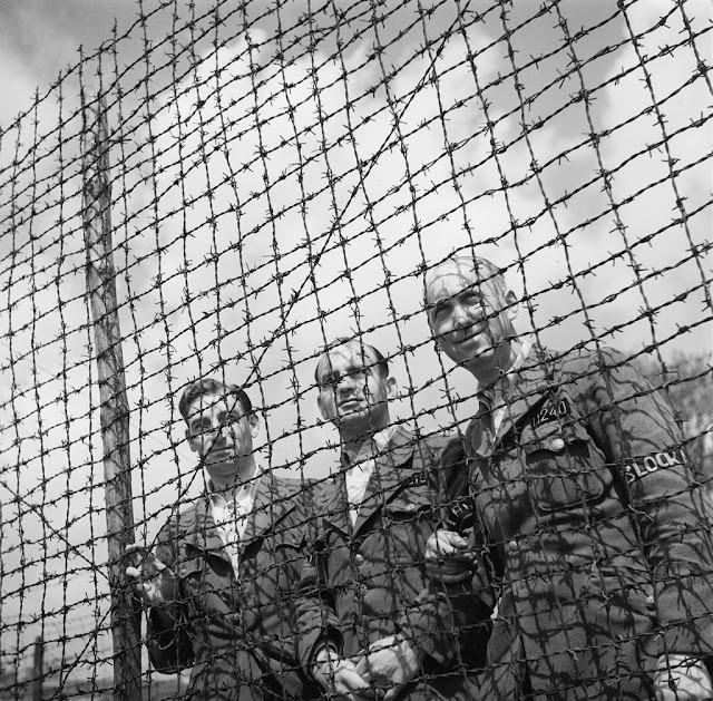 Liberation of the concentration camp Amersfoort. Three Dutch army officers behind barbed wire. From the collection of the Nationaal Archief of the Netherlands.