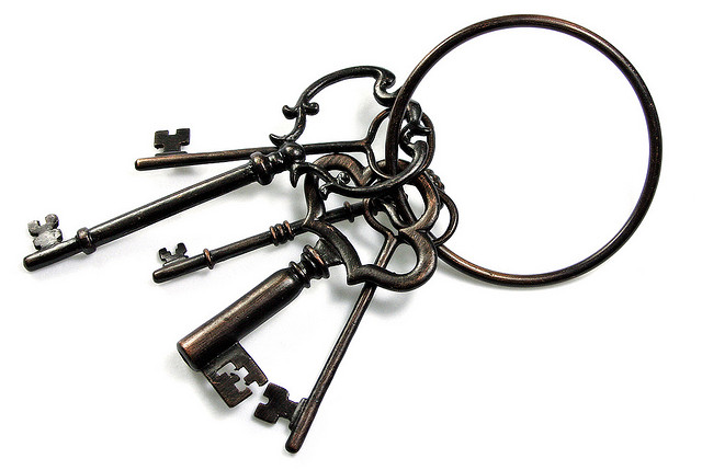 A set of old, metal keys on a large metal key ring