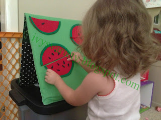 toddler using handmade felt watermelon seed counting activity