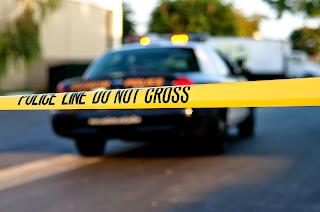 Police car behind crime scene tape.