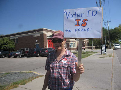 Man holding hand-made sign reading 'Voter ID' Is the Fraud