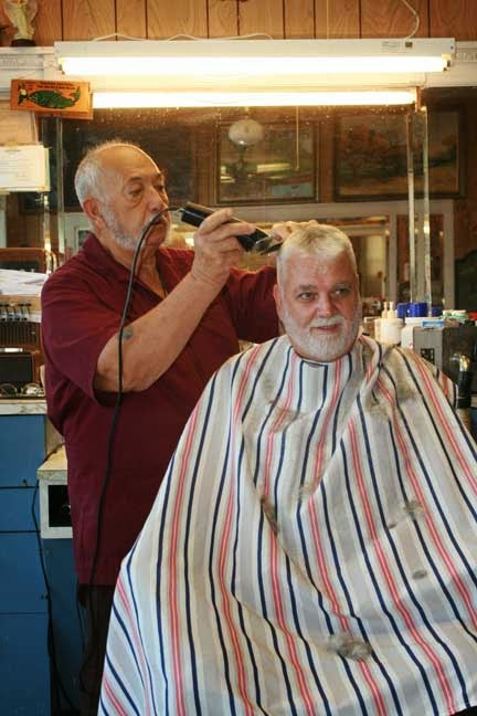 ... , gives John Hamm a trim Friday, Sept. 5, at the Stover Barber Shop
