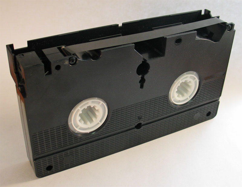 Photograph Of Bottom Side Of A VHS Cassette With Tape Exposed