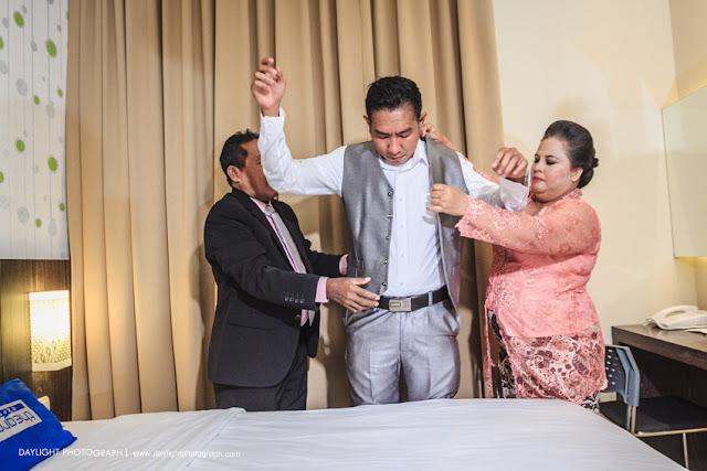 foto pernikahan, lokasi di hotel The Groove Yogyakarta, saat Mike, calon pengantin laki-laki dibantu orang tua mengenakan jas sebagai  persiapan p;emberkatan pernikahan di Gereja Adven Timoho Yogyakarta