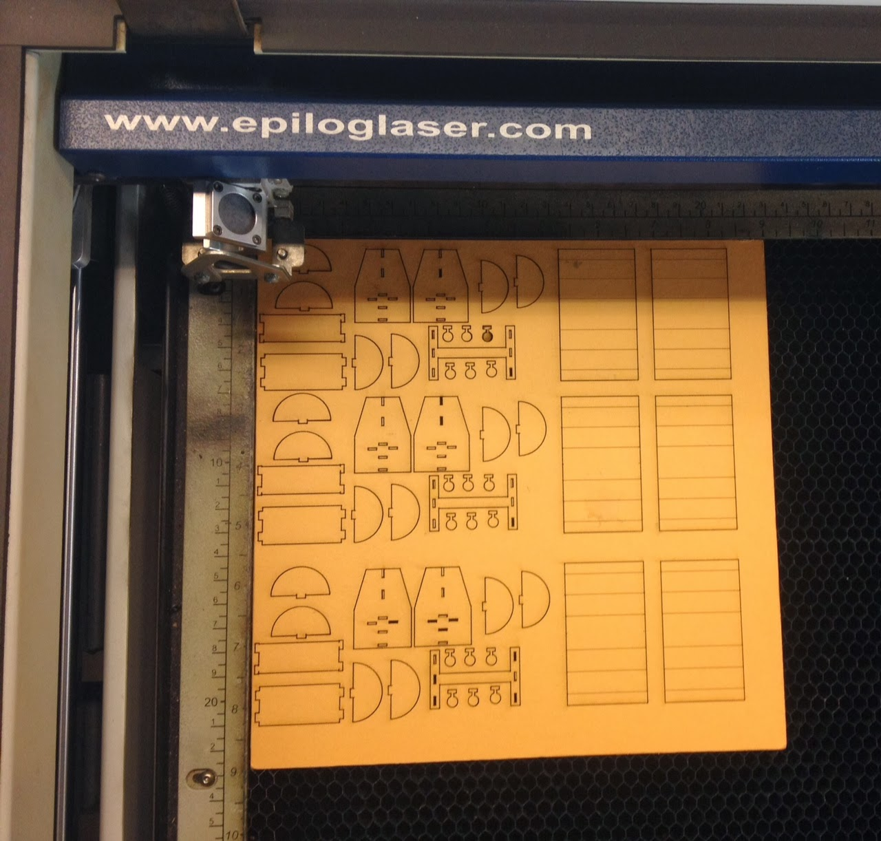 Image shows laser cut wooden template of miniature exhibit kiosk models to be assembled.