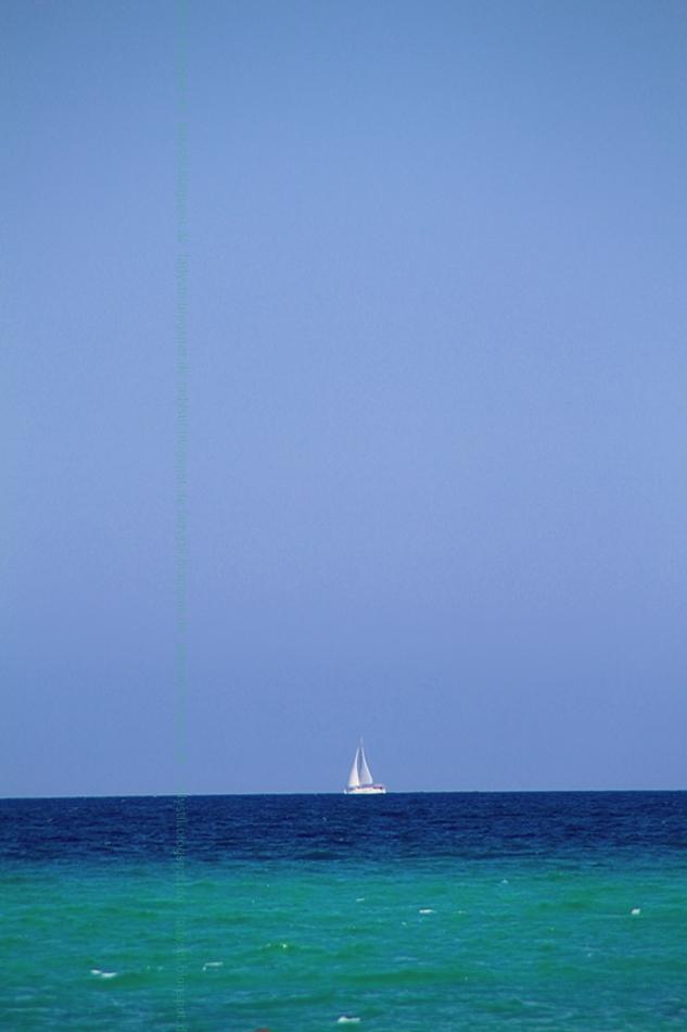 Blick übers türkisfarbene Meer mit weißem Segelboot und strahlendblauem Himmel