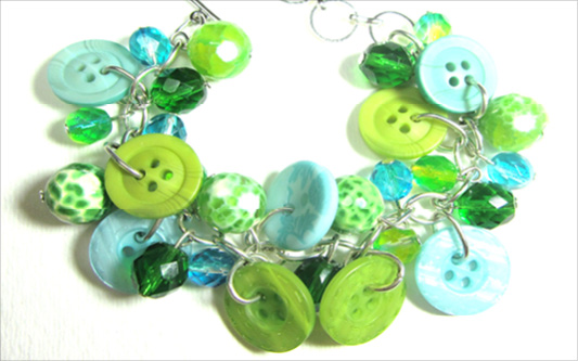 Bracelet has green and teal buttons with beads in pretty charm style design