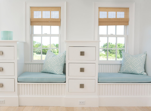 two short window seats divided by a white drawers with blue cushions and blue and white geometric print accent pillows