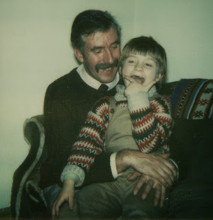 Cute 1980s photo of a boy sitting on his dad's lap