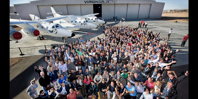 A majority of Virgin Galactic's future Astronauts gather with Sir Richard Branson (center) for a group photo at Virgin Galactic FAITH hangar in Mojave, CA September 25, 2013. AT side is the WhiteKnight2 mated with SpaceShip2. Credit: Mark Greenberg