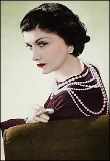 Coco Chanel c. 1936, with red lipstick and strands of pearls