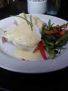 Two eggs, benedict style, smothered in hollandaise sauce and with an interesting side salad