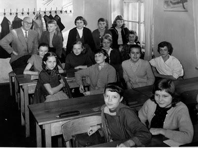 Eine Schulklasse in denn 1950-er Jahren mit Lehrer und Schulbänken.