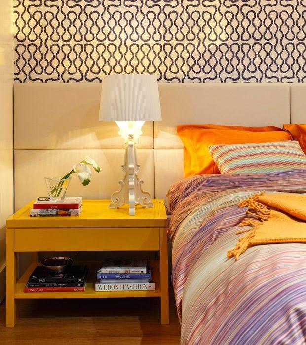 Criado mudo amarelo, papel de parede e painel de cama com estofado