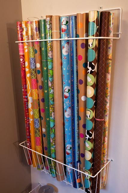 I store my wrapping paper on top of the cabinets in my laundry room with a rubber band wrapped around both ends of each roll. The moulding keeps them from rolling off the cabinets. I use a small step-stool (stored in the laundry room) to retrieve and return the appropriate roll .
