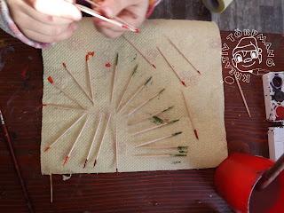 Szöveg: A kiszínezett (végű) pálcikákat hagyjátok megszáradni, majd a Marokkó játék szabályait alkalmazva kezdjetek el játszani! Kép: Közelkép egy papírtörlőre rakott, száradó fogpiszkáló halmaz fölött működő gyermekkézről. A papírtörlő mellett vízfesték részlet és pohár részlet látszik.