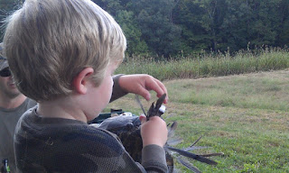 Kid stuffing dove feathers in a hat